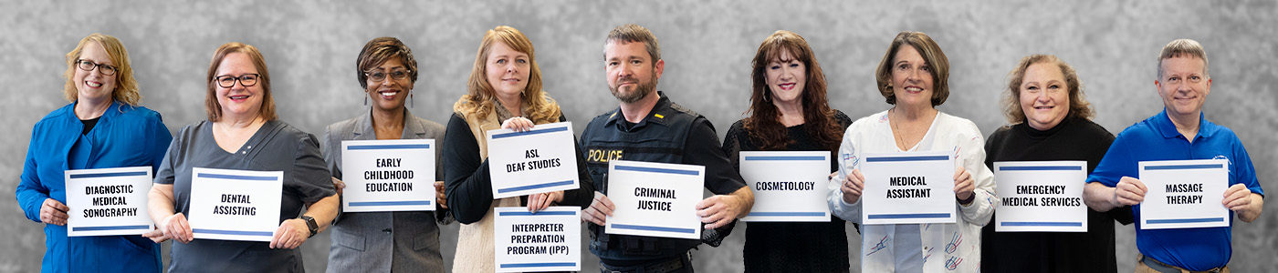 Instructors holding signs for programs within Allied Health and Public Service