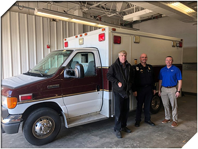 Bruce Davey(Fleet Manager at JC Ambulance), Kenton Schafer(Director at JC Ambulance), and Scott Wernsman standing next to ambulance
