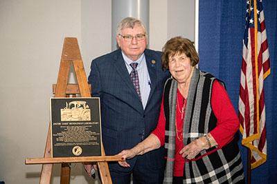 "Carolyn Rendleman with husband Jake Rendleman and plaque for Jacob ""Jake"" Rendleman Laboratory"